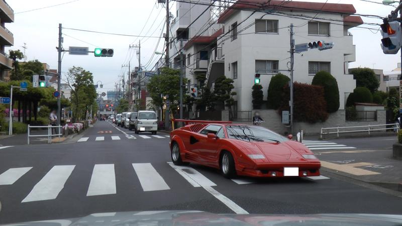 交差点を横切る真っ赤なランボルギーニ・カウンタックの画像です